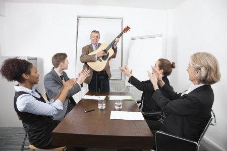 Businessman playing guitar in meeting