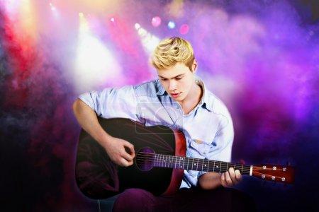 Photo pour Jeune homme caucasien, jouer de la guitare en concert - image libre de droit