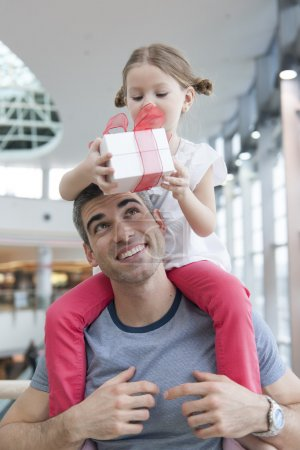 Daughter sits on fathers shoulders