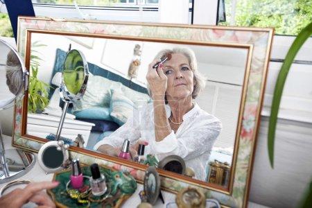 Senior woman applying blusher