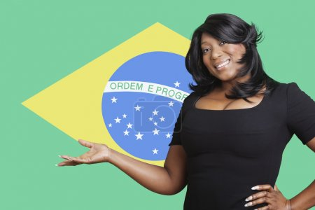 Woman holding out empty palm over Brazilian flag