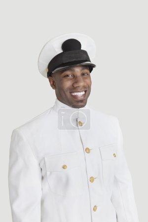 Photo pour Portrait de joyeux jeune officier de la marine afro-américaine debout sur fond gris - image libre de droit