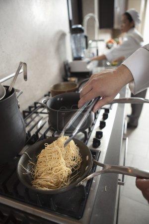 chef heating spaghetti on hob