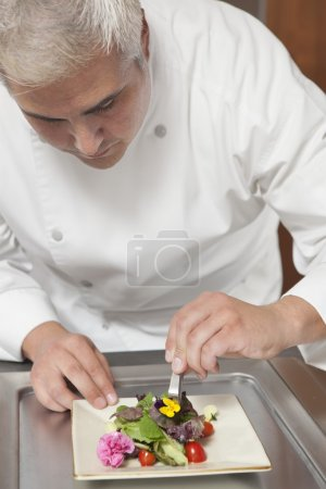 chef arranges edible flowers on salad