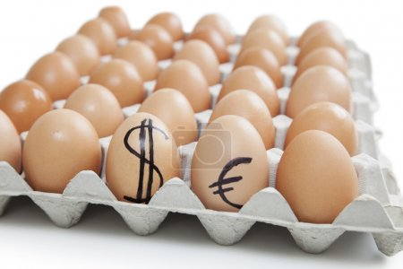 Eggs in carton with dollar, euro sign