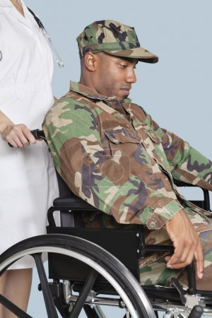 Photo for Sad US Marine Corps soldier wearing camouflage uniform in wheelchair assisted by female nurse - Royalty Free Image