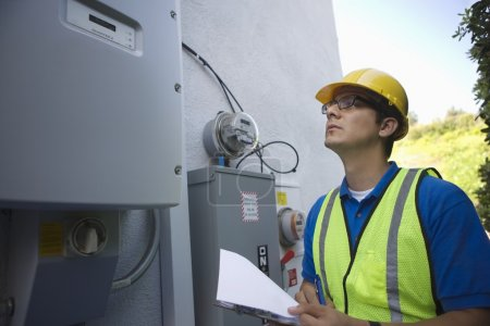Maintenance worker reads meter of solar generation unit