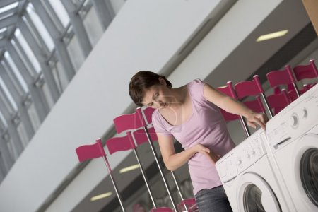 Young woman measures washing machine