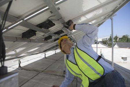 Maintenance worker adjusting solar panel