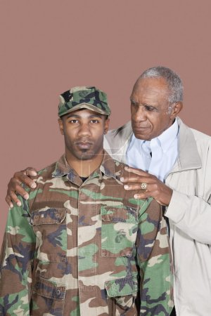 Photo for Portrait of African American male US Marine Corps soldier with father over brown background - Royalty Free Image
