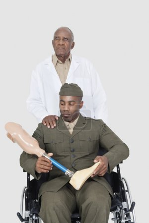 Photo for Senior doctor standing behind military officer holding artificial limb as he sits in wheelchair over gray background - Royalty Free Image