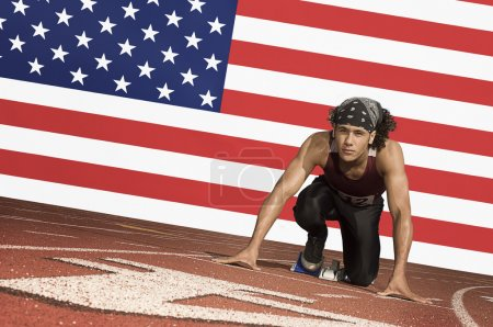 Photo for Runner on a track in starting block in front of American flag - Royalty Free Image