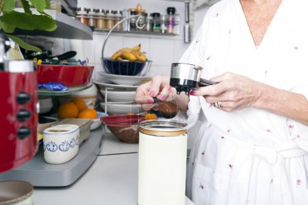 Senior woman filling ground espresso