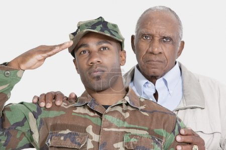 Photo for Portrait of US Marine Corps soldier with father saluting over gray background - Royalty Free Image