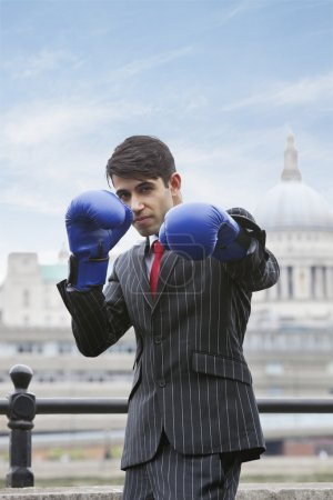 Indian businessman wearing boxing gloves