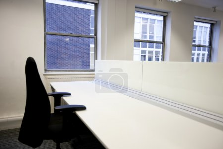 Office chair and empty desk by window