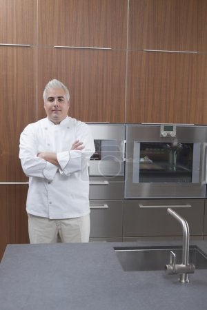 Mid- adult chef stands with arms folded