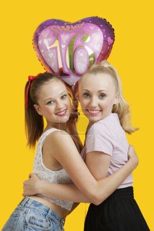 Women with birthday balloon hugging