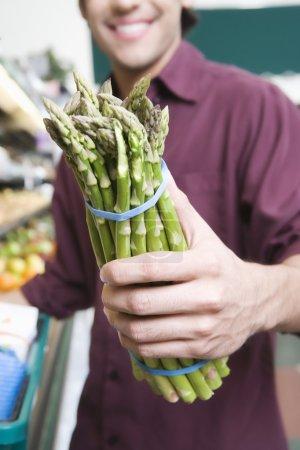 man holding asparagus