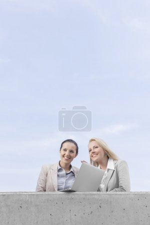 businesswomen with laptop looking away