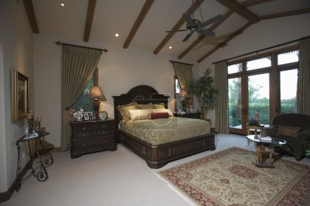 Bedroom with beamed ceiling and patio