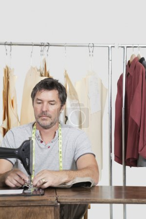 Male dressmaker stitching cloth