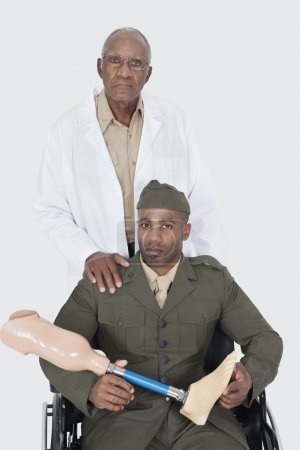 Photo for Portrait of senior doctor standing with military officer holding artificial limb as he sits in wheelchair over gray background - Royalty Free Image