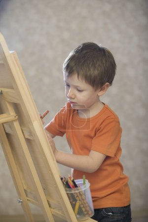 Young boy drawing on a canvas