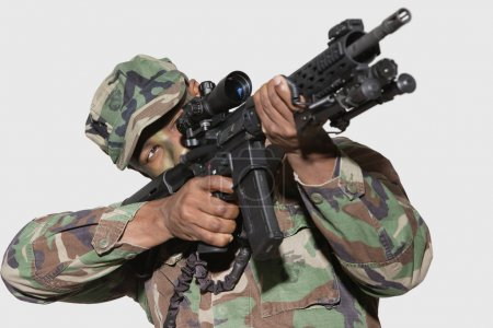 Photo for US Marine Corps soldier aiming M4 assault rifle against gray background - Royalty Free Image