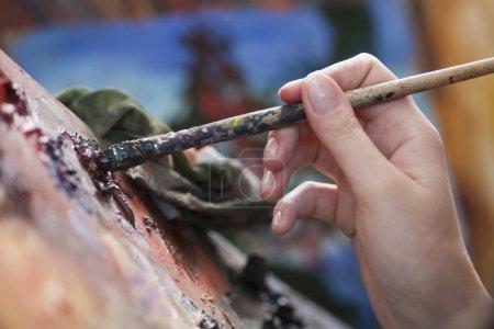 Woman holds paintbbrush