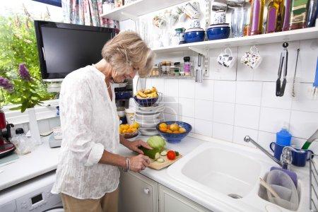 Senior woman chopping fresh vegetables