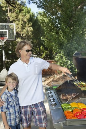 Boy with father barbecuing vegetable