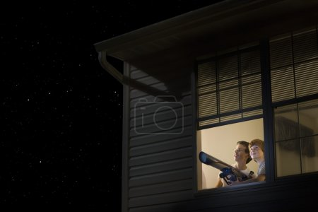 Teenage boys with telescope at night