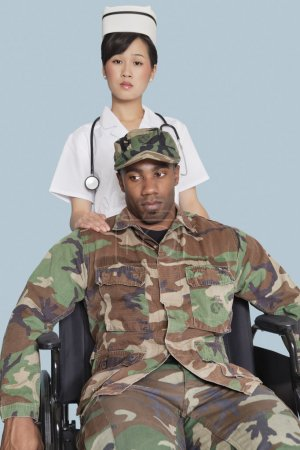 Photo for Female nurse comforting disabled US Marine Corps soldier in wheelchair over light blue background - Royalty Free Image