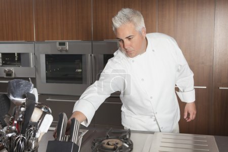 Mid adult chef leans for knife
