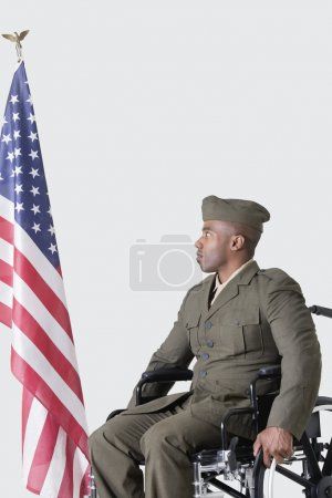 Photo for Young military soldier in wheelchair looking at American flag over gray background - Royalty Free Image