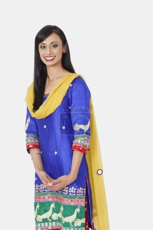 Photo pour Portrait de belle indienne traditionnelle tenue debout sur fond gris - image libre de droit