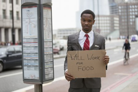 Businessman holding sign Will Work for Food