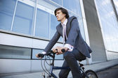Young businessman riding bicycle