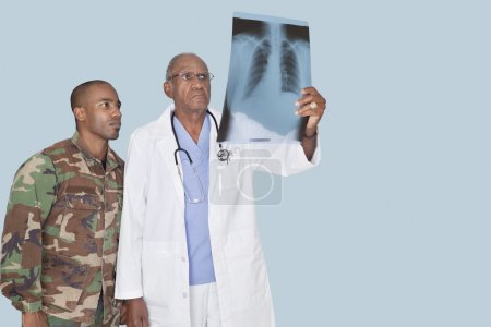 Doctor with soldier looking at x-ray report