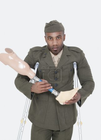 Photo for Portrait of a disabled military officer holding prosthesis leg with crutches standing over gray background - Royalty Free Image