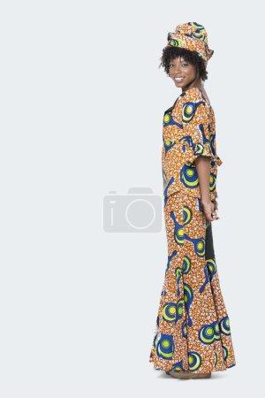 Photo pour Portrait pleine longueur de jeune femme en costume imprimé africain debout sur fond gris - image libre de droit