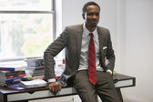 African American businessman sitting on office desk
