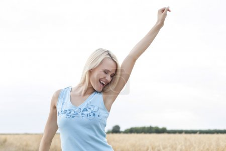 Photo for Cheerful young woman with arm raised standing against clear sky - Royalty Free Image