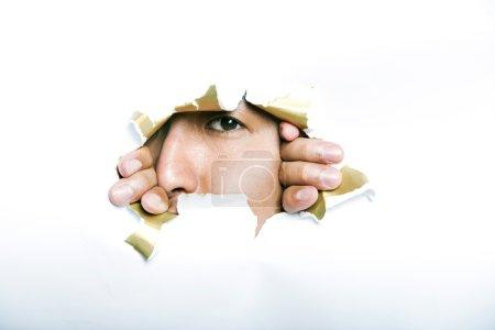 Mann blickt durch aufgerissenes Papierloch