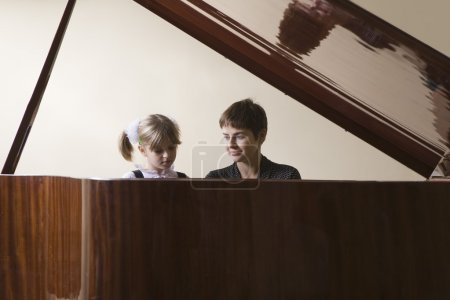 little girl and teacher at piano