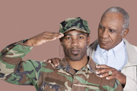 Photo for Portrait of US Marine Corps soldier with father saluting over brown background - Royalty Free Image