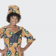 Portrait of young woman in African print attire st...