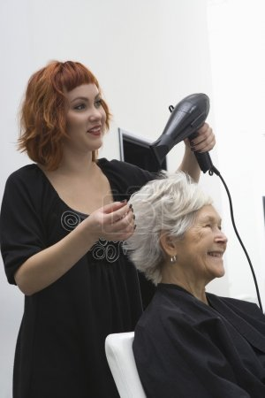 Photo for Stylist blow-drys elderly woman's hair - Royalty Free Image