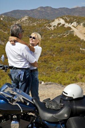 Senior couple embrace next to motorcycle